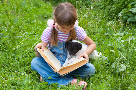 A girl reading  book with little puppy in garden photo