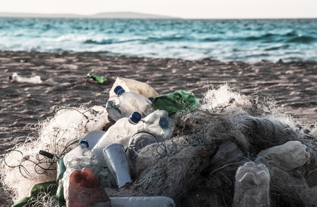Beach pollution  Plastic bottles and other trash on sea beach photo