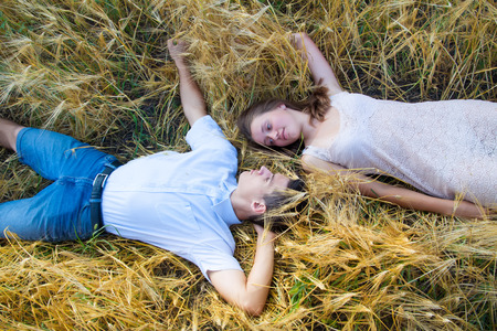 happy smiling souple relaxing on wheat field  Young couple lying on grass outdoor photo