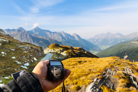 GPS navigator and hand on Alps mountain background