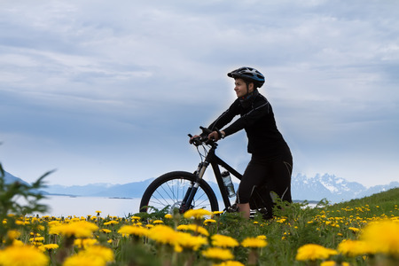 off road biking: Mountain bike cyclist at flowered field, Lofoten, Norway Stock Photo
