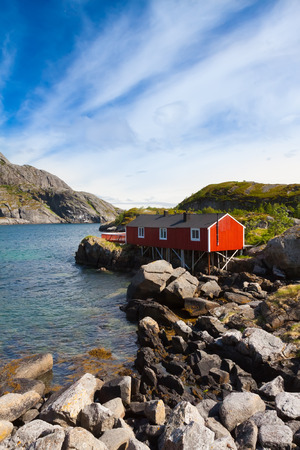 rorbu: Typical red rorbu, fishing hut invillage Nusfjord on Lofoten islands in Norway lit by midnight sun
