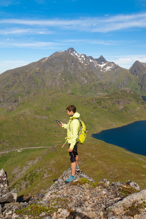 hiker young woman in hight mountains holding in her hand GPS navigator, Lofoten, Norway photo
