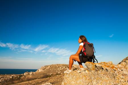trekker: woman hiker with backpack sits on seaside mountain rock