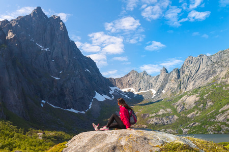 Young tourist woman is sitting  on stone near mountain lake Kallevatnet and looking at beautiful landscape photo