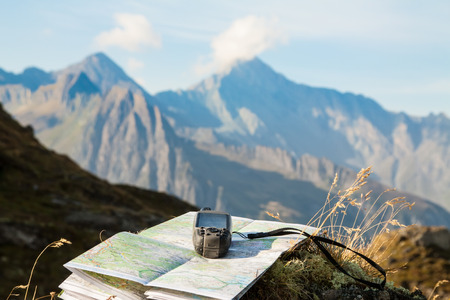 adventure travel: GPS navigator and map on Alps mountain background