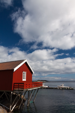 rorbu: Typical red rorbu fishing hut in town of A village on Lofoten islands in Norway lit by midnight sun Stock Photo