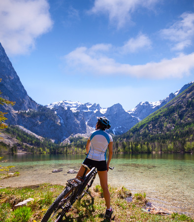 cycleway: Young woman riding bike beside a lake in  Alps,  Salzkammergut Austria