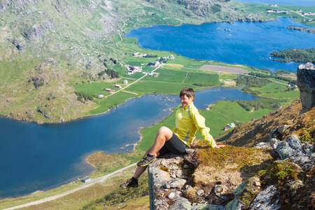 crack climb: Sporty woman on the top of a mount Holandsmelen, Lofoten, Norway