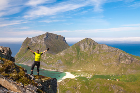 crack climb: Sporty man on the top of a mount Holandsmelen, Lofoten, Norway Stock Photo