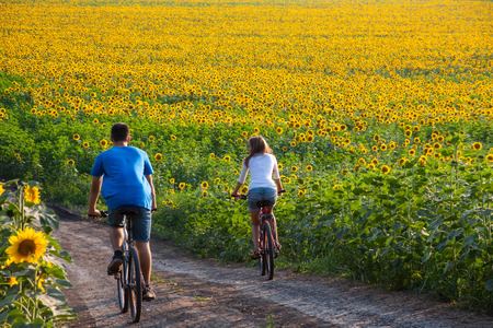 Two happy teen cyclist in sunflower field riding bicycle
