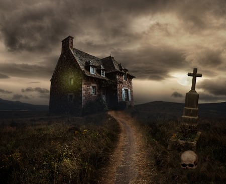 spooky house: Apocalyptic Halloween scenery with old house, skull and grave Stock Photo