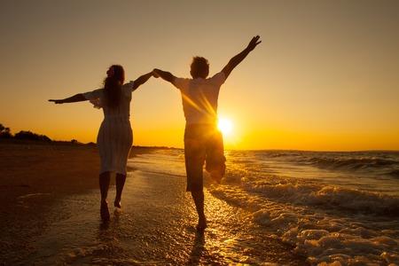 amantes: Pareja feliz corriendo en la playa en la puesta del sol