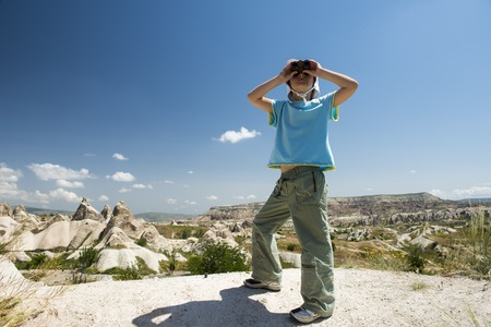 looking ahead: Small tourist girl with binocular in mountains looking ahead