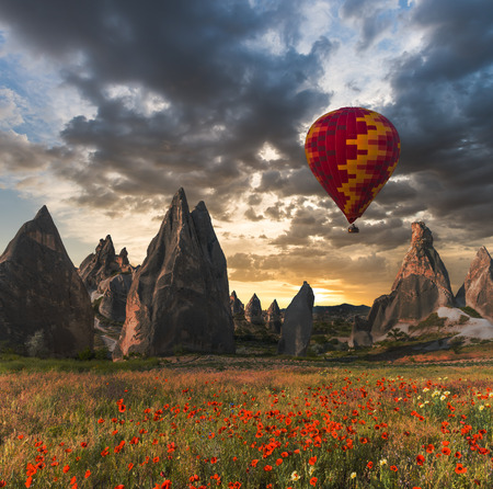 adventure aeronautical: Hot air balloon flying over red poppies field Cappadocia region, Turkey Stock Photo