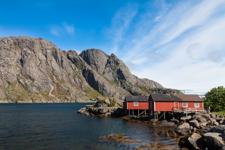 rorbuer: Typical red rorbu, fishing hut invillage Nusfjord on Lofoten islands in Norway lit by midnight sun