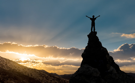 man on the top of a rock meeting sun