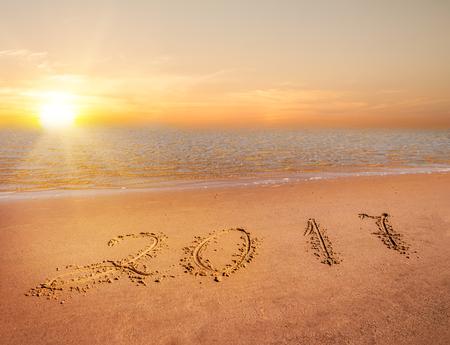 new year 2017 digits on ocean beach sand