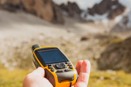 walking paths: GPS navigator in hand against Dolomites Alps Stock Photo