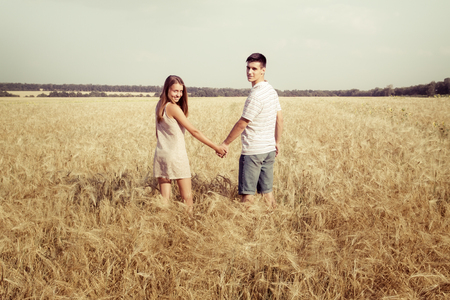 Young inlove couple walking in field at sunset holding hands
