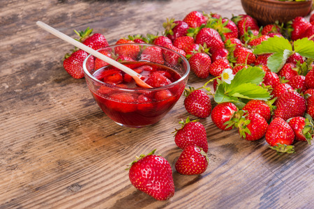 summer fresh red strawberry and jam on wood background