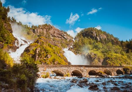 Summer Latefossen Waterfall Odda Norway with the stone road bridge. Latefoss is a powerful, twin waterfall, famous sightseeing