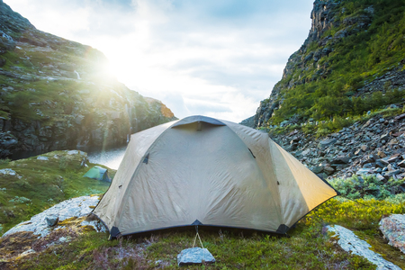 tourist tent near mountain lake, summertime sunset, Norway Stock Photo