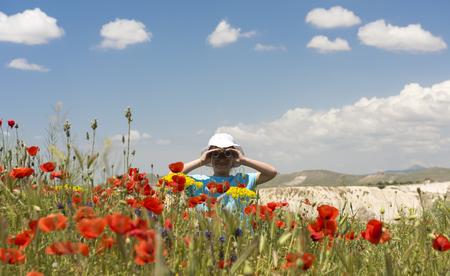 Little girl looking through binoculars in summer field