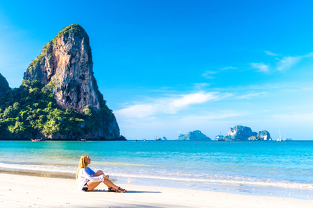Woman resting on amazing Railay beach in Krabi Thailand. Tropical resort.