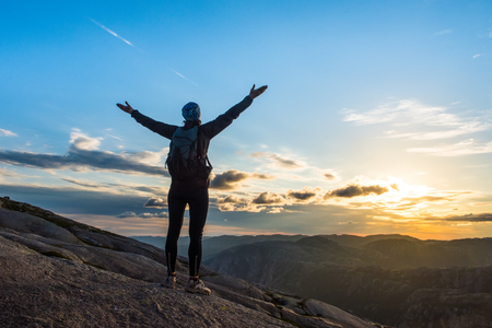 Woman successful hiking silhouette in mountains, motivation and inspiration in beautiful sunset. Female hiker with arms up outstretched on mountain top, inspirational landscape