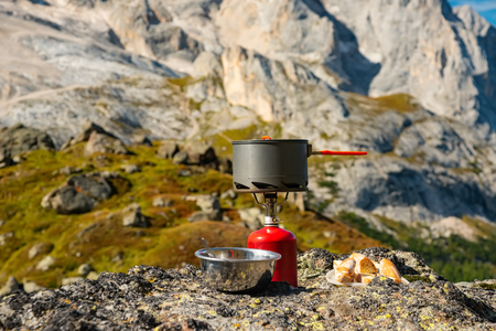 Tourist equipment and tools: camping gas over Marmolada mountain background Dolomites Italy Banco de Imagens