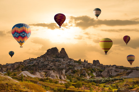 Colorful hot air balloons flying over the valley at Cappadocia, Uchisar, Turkey. Volcanic mountains in Goreme national park Imagens