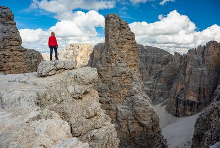 Escursionista attivo che fa escursioni, godendosi il panorama, guardando il paesaggio delle montagne delle Dolomiti. Concetto di stile di vita sportivo di viaggio