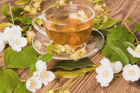 Cup of green tea linden jasmine on wooden background