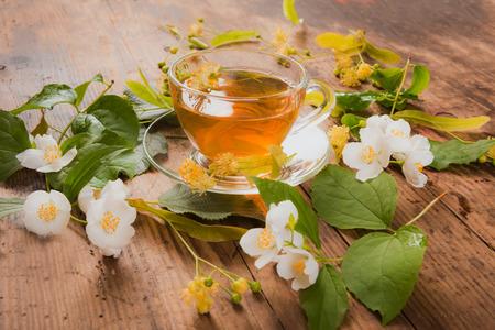 Tazza di tè verde tiglio gelsomino su sfondo di legno