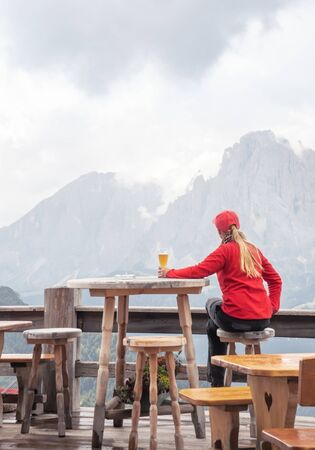 Sporty woman drinking beer in mountain cafe. People and Lifestyles concept. Travel and adventure