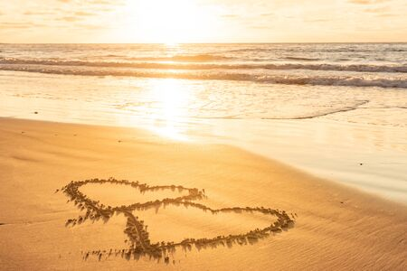 Valentines day on sunny beach. Two hearts drawn in sand, love concept Stock Photo