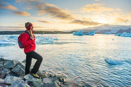 Sporty woman near Ice Glacier Lagoon Jokulsarlon over sunset. Icebergs drifting towards the sea. Great tourist spot of Iceland.