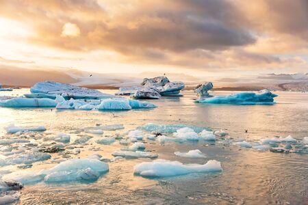 Icebergs floating in Jokulsarlon glacier lagoon lake at sunset. Great tourist attraction in Iceland Gold Circle. Foto de archivo - 140907371