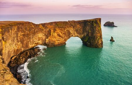 Natural lava arch in the sea. Cape Dyrholaey, coast of Iceland. Popular tourist attraction. Beauty world. Archivio Fotografico