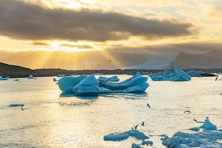 Icebergs floating in Jokulsarlon glacier lagoon lake at sunset. Great tourist attraction in Iceland Gold Circle. Foto de archivo - 140907380