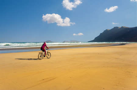 Sporty young woman ride bicycle on sand Famara beach. Lanzarote Canary Island