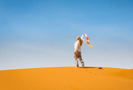 Sporty woman in Merzouga dunes of Sahara desert Morocco