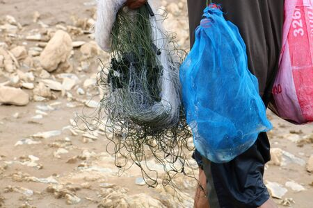 The Mekong River fishermen in Thailand are putting fish in their bags.