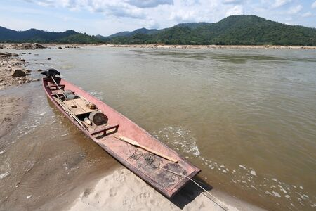 Local fishing boat by the sand on the Mekong River in Pak Chom District, Loei Province, Thailand