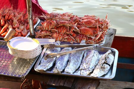 Popular seafood is sold on the boat at Amphawa Floating Market, Samut Songkhram Province, Thailand. Imagens - 130205747