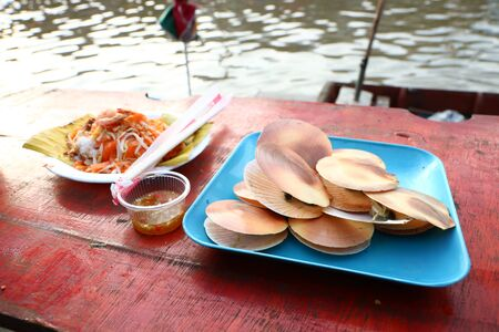 Toasted scallops are popular in the floating market, Amphawa District, Samut Songkhram Province, Thailand. Imagens