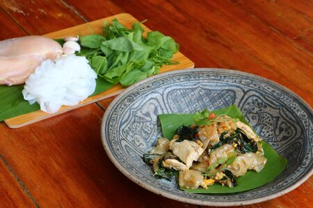 Stir fried ribbon noodle with vegetables, Chiang Da, which is a native herb in northern Thailand.