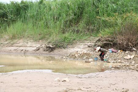 Villagers surveying gold ore on the banks of the Mekong River in Pak Chom District, Loei Province, on 31 August 2019