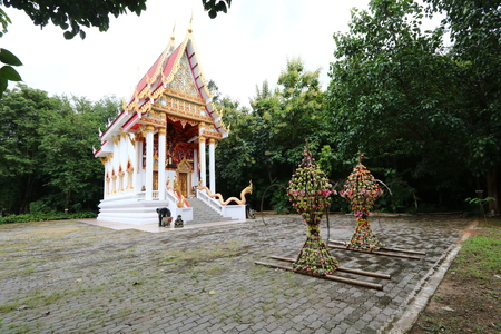 A floral frame is placed in front of the church of a Thai Buddhist temple in the countryside. Editorial